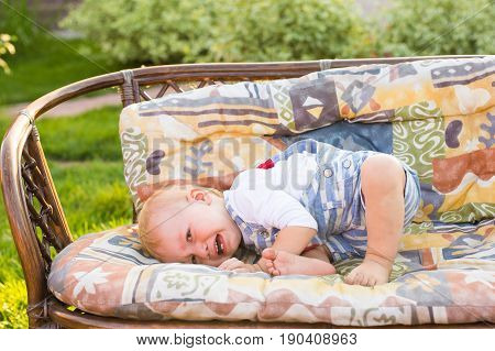 Cute unhappy baby boy with blond hair crying outdoors on sunny summer day.