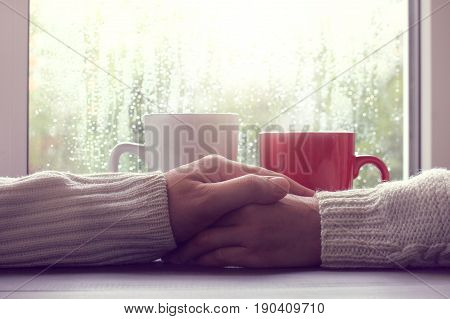 Two people hold each other's hands against a background of cups and a window with drops after a rain/ Warmer feelings together in any weather