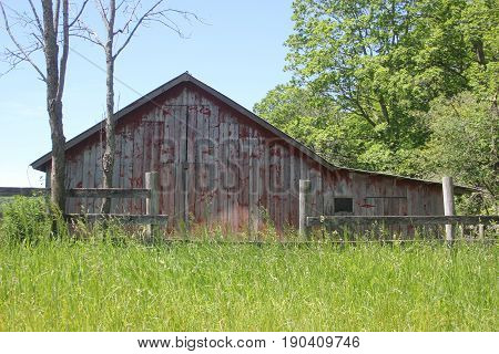 A barn with a fence and long grass