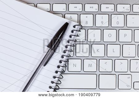 Notepad And Pen On Computer Keyboard