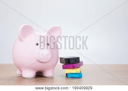 Printer Cartridges Next To Piggy Bank