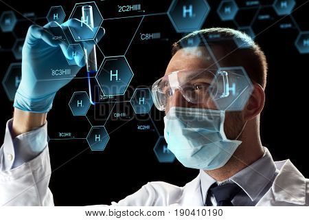 science, research and chemistry concept - young scientist in safety glasses, face mask with test tube and virtual projection of chemical formula