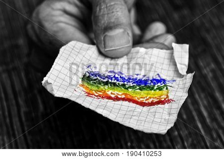 closeup of a young caucasian man in black and white with a piece of paper in his hand with a colorful rainbow flag painted in it