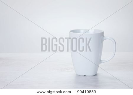 Plain white generic ceramic coffee mug on a textured off-white background with copy space alongside