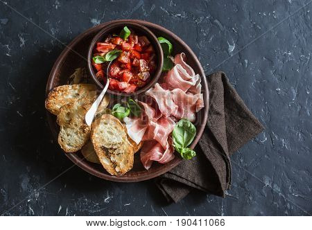Italian antipasto - tomatoes bruschetta and prosciutto. On a dark background top view. Delicious snack or appetizer for wine