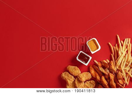 Nuggets and Chips. Nuggets and french fries in red paper box. Fast food on red background. Nuggets with tomato sauce. Top view, flat lay with copyspace