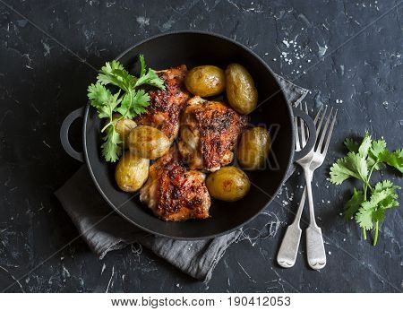 One pot baked harissa chicken and new potatoes on a dark background top view