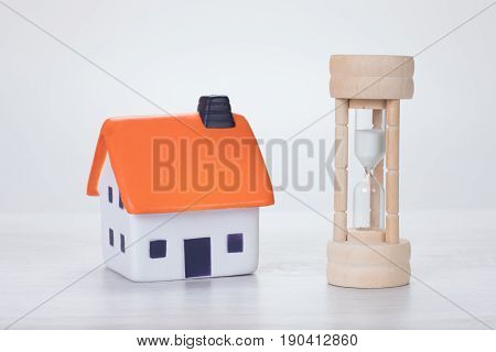 Wooden Egg Timer Alongside A Model House
