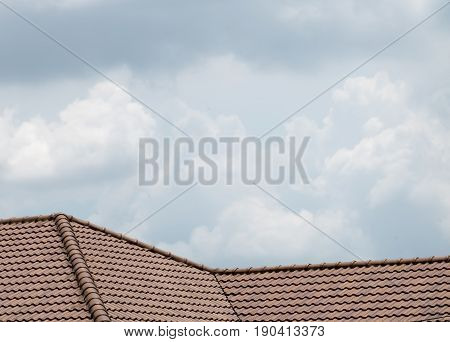brown peaked roof. a roof top with red tiles. brown roof on sky background.