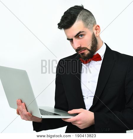 Online business idea. Busy and strict businessman with beard stylish haircut and red bow tie holds white laptop isolated on white background. Digital marketing concept