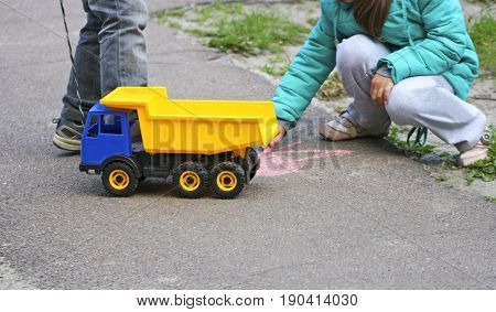 Children play in the fresh air. The image of the children who play near paved roads. The girl draws with chalk on the pavement. In the hands of a bright boy a toy car.