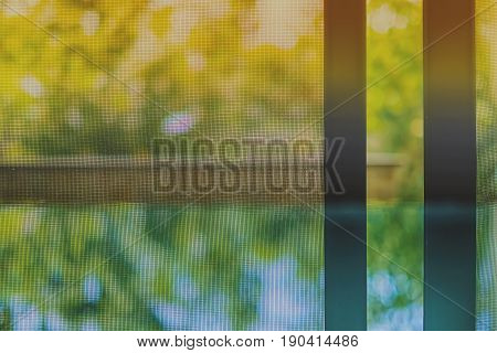 Opened door wire mesh screen with blurred natural background and vintage retro color tone
