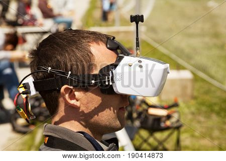 Khabarovsk Russia - May 21 2017: Drone pilot wearing first-person view headset. Young man driving a quadcopter using video-goggles