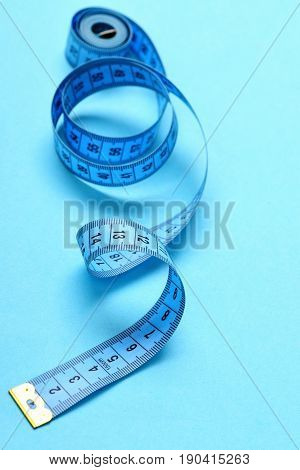 Roll Of Untwisted Tape For Measuring On Light Blue Background.