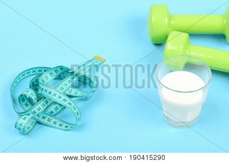 Glass Of Milk Near Green Dumbbells And Untwisted Measuring Tape