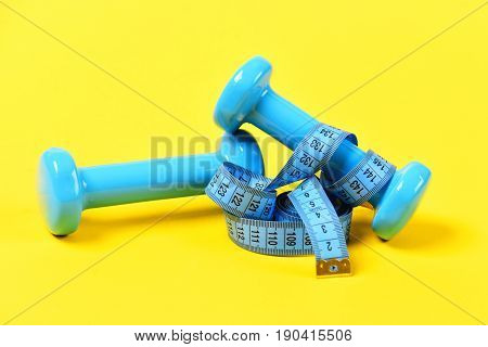 Centimeter And Barbell Or Dumbbells On Yellow, Aerobics Concept