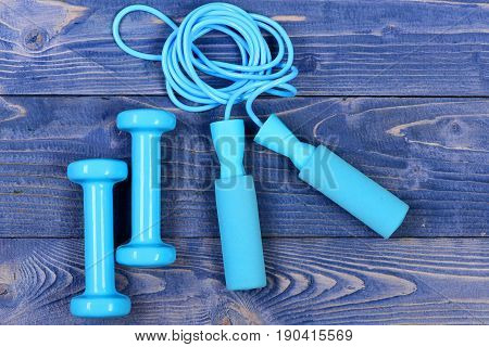 skipping rope and dumbbells on blue vintage wooden background