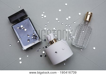 Different bottle of perfume in grey background