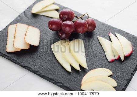 gourmet mixed cheese board tapas starter with apple and grapes snack