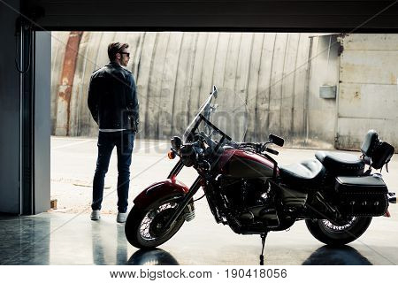 Back View Of Stylish Young Man In Leather Jacket Standing Near Motorbike And Looking Away