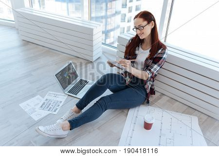 Pleasant work. Nice delighted beautiful woman sitting on the floor and working while being surrounded by drawings and drafts