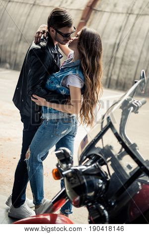 Stylish young couple hugging and kissing while standing near motorbike