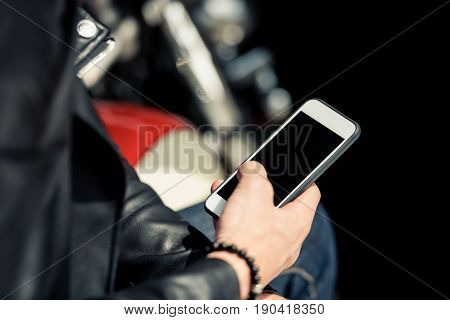 Close-up partial view of man in leather jacket using smartphone with blank screen
