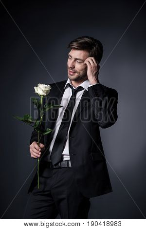 Young Man In Suit Holding White Rose And Looking Away Isolated On Black