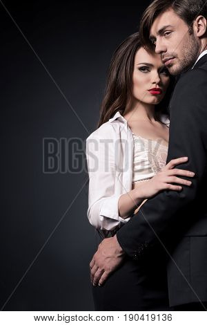 Beautiful Sensual Couple Embracing Ang Looking Away Isolated On Black
