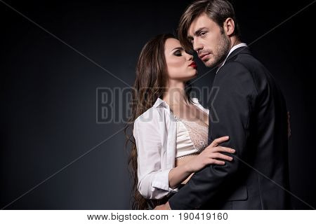 Young Sensual Couple Embracing And Able To Kiss Isolated On Black