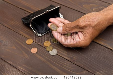 An Elderly Man Holding An Old Coin Purse And Coins . The Concept Of Poverty In Retirement.