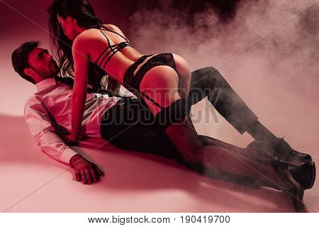 Young Sensual Couple Embracing In Foreplay While Lying On The Floor
