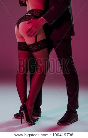 cropped shot of man touching buttocks of sexy woman in lingerie