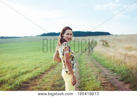 Young girl with long brown hair stays at the road field. warm tinted.