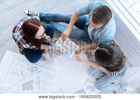 Modern building. Professional hard working intelligent architects working together and discussing a blueprint while designing a modern building