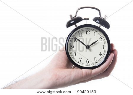 Man holding an old-fashioned alarm clock with a round dial and bells cupped in the palm of his hand isolated on white with copy space