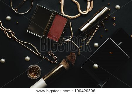 Makeup cosmetics products and accessories on dark background