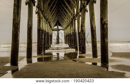 Under The Boardwalk. Waves crash under an Atlantic Ocean pier in Myrtle Beach, South Carolina.