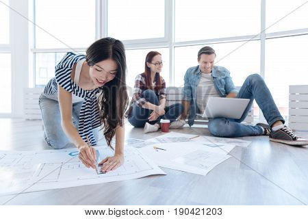 Architecture blueprint. Joyful nice Asian woman using a pencil and a ruler and drawing while working on an architecture blueprint
