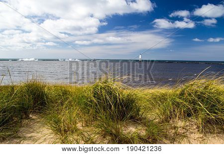 Summer Beach Panorama. Dune grass on the beach with sunny blue sky and lighthouse in the background on the Lake Michigan coast. Frankfort, Michigan.