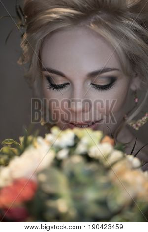 Happy beautiful bride with bright make-up and voluminous hairdress looks at her bright bouquet and smiles