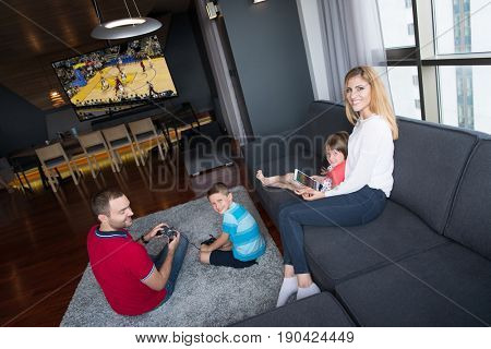 Happy family. Father, mother and children playing a basketball video game Father and son playing video games together on the floor