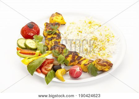 Crispy grilled chicken kebab with rice herbs salad and grilled tomato arranged on a plain white plate. High angle view studio shot over white clean tabletop. Fusion food concept for Persian dish.