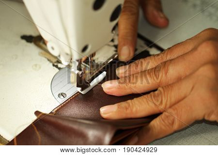 Old women's hands with sewing machine at textile factory