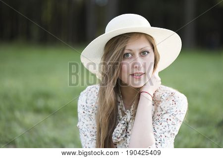 The face of a beautiful girl with long blond hair large green eyes long black eyelashes a smile on her face a white hat and a white dress with a floral pattern on the background of green grass.