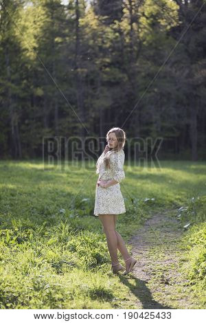 Beautiful girl with long blond hair in a short white dress is standing on a path on the green grass near the forest. The hand lies on the waist the girl looks down.