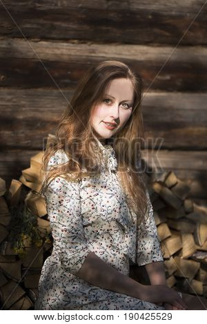 A beautiful girl with blond long hair and green eyes in a white dress with a floral pattern sits near an old wooden house against the backdrop of punctured birch firewood.