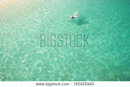 Woman snorkling and relaxing crystal clear and turquoise sea water of the tropical sea .
