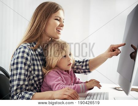 Cheerful young mother with daughter browsing on computer sitting at the table. Concept of family online shopping and booking.