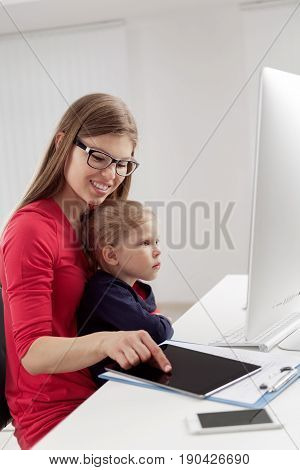Family, technology and networking. Pretty smiling woman browsing internet with tablet pc, holding her cute girl in home office.